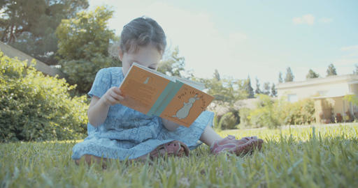 Little girl sitting outside reading a children's book Footage