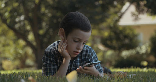 young boy sitting outdoors playing with a smartphone Footage