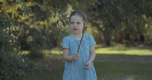 Cute little girl wearing a dress playing outdoors in the sun Live Action