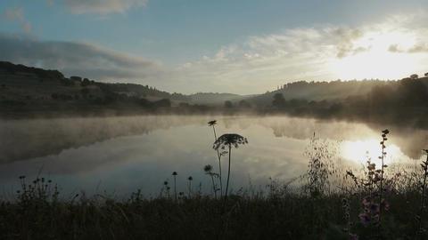 Fog rising from a lake at sunrise