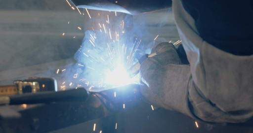 Welder welding metal parts in a metal workshop Live Action