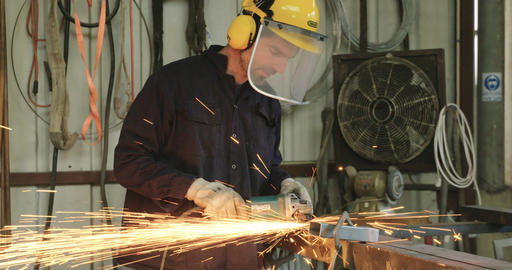 Worker using a metal grinder in a metal workshop Footage