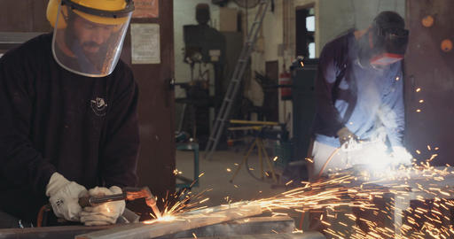 Welders welding metal parts in a metal workshop Footage