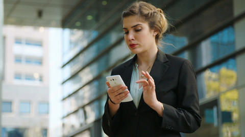 Business woman walking on the street and talking on the mobile phone