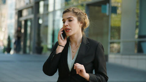 Business woman walking on the street and talking on the mobile phone 圖片