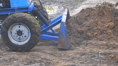 A wheeled tractor fills the trench with a bucket Live Action