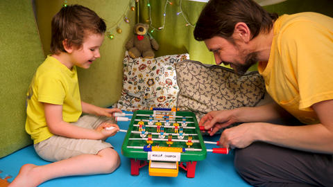 Playing table football. Happy childhood concept. One parent family. Enjoying Live Action