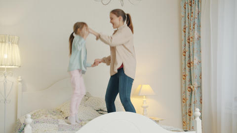 Mom active young woman having fun with cute little daughter at home jumping in Live Action
