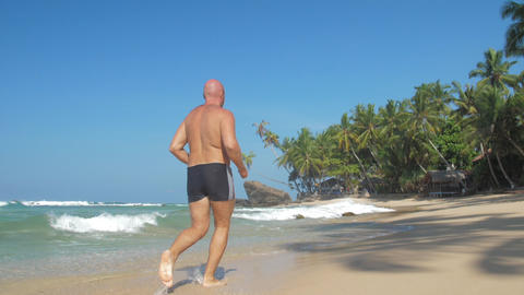 man supports healthy lifestyle jogging along wet beach Live Action