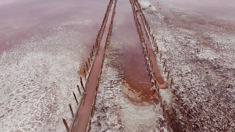 Old pier on pink lake medicinal clay ungraded on sunset, air drone view Live Action