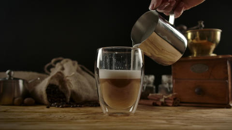 Pouring frothed milk from barista pitcher into glass mug with coffee. Making Live Action