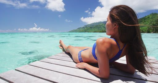 Woman in bikini at Luxury travel vacation destination on overwater bungalow Live Action