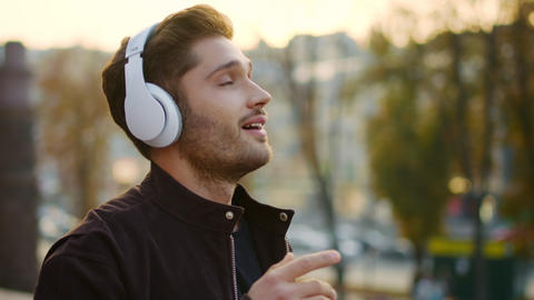 Emotional man listening music headphones outside. Excited guy singing on walk Live Action