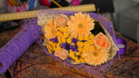elegant bouquet with orange and purple flowers on table Live Action