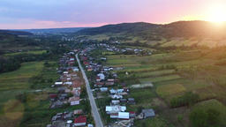 Aerial view of countryside village and crops at sunset Footage
