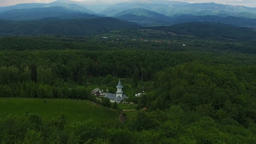 Christian church surrounded by green forest, aerial flight, Ciocanu Monastery in Footage