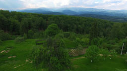 Christian church on top of green hill with mountain range, cam fly Footage