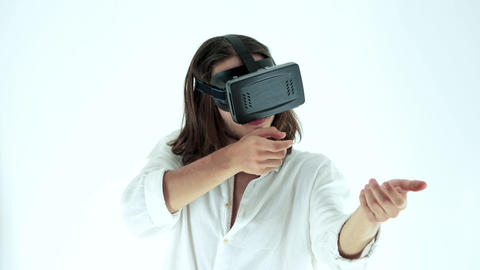 Young man wearing virtual reality headset in Studio Shot. He shows gestures while playing video game GIF