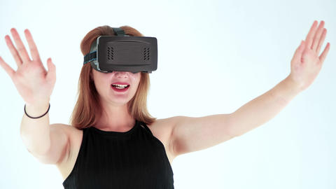 Young woman wearing virtual reality headset in Studio Shot. She shows gestures while playing video GIF