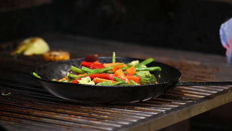 Chef is cooking vegetables in commercial charcoal grill Live Action