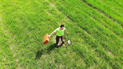man alone men spinning in a green field, holding suitcase in a hand, funny Live Action