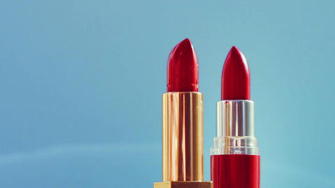 Two chic red lipsticks on blue background and shining light flares, luxury make Live Action