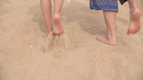 Barefoot woman and girl walking on sandy beach at sea. Back view barefoot women Live Action