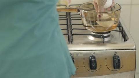 woman puts four white eggs inside a glass pot with water on the stove ライブ動画
