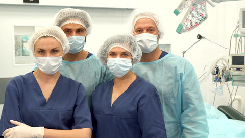 Two surgeons and two nurses pose at the surgery room Live Action