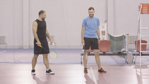 Wide shot of sportsmen training badminton hand movement indoors. Portrait of Live Action