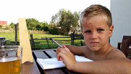 Little boy doing homework and making faces Footage