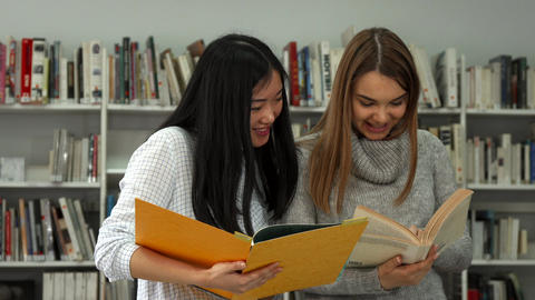 Two female students compare information in two books at the library Live Action
