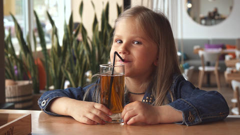 Little girl drink some flavored water at the cafe Live Action
