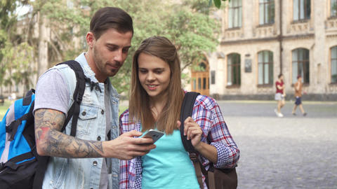 Students watch images on smartphone on campus Live Action