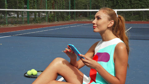 Tennis girl surfing the net while relaxing Live Action
