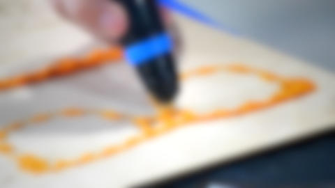 Blurred background. 3d drawing pen. A man draws a figure in the form of glasses Live Action