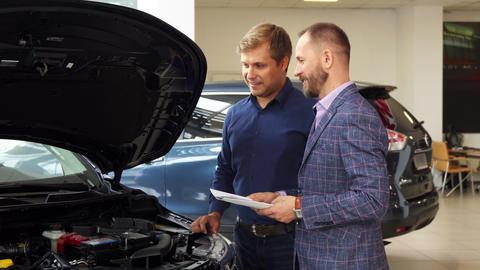 A representative man chooses new car in the car salon Live Action