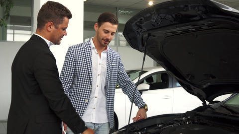 A professional salesman acquaints a buyer with a car engine Live Action