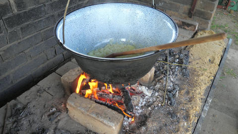 Old man adding wood into fire. Cooking in garden kitchen, adding onions in enamel cauldron and Live Action