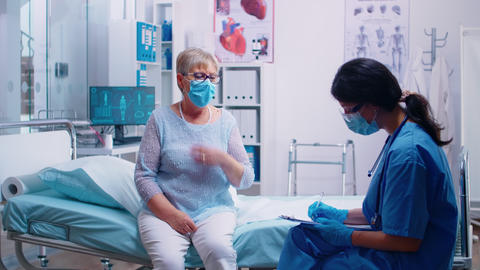 Nurse talking with old senior patient Live Action