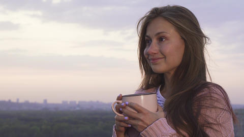 A young girl drinks a warm drink and enjoys the sunset Live Action