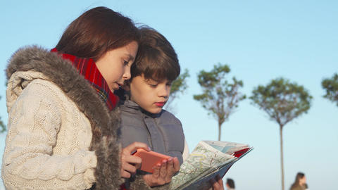 Active children try to find the next place of their route with a map and mobile phone Live Action
