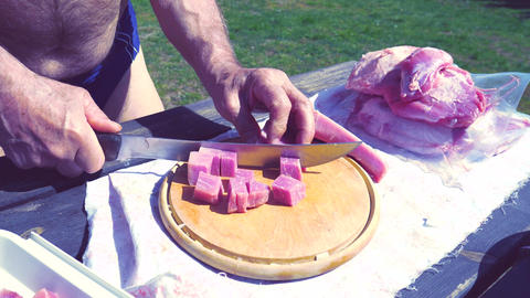 Man cut pork meal for goulash. Cubed and sliced piece pork meat on wooden board. Nice fresh raw Live Action