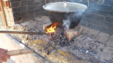 Grandpa puts dry birch wood under a cauldron with an aluminum lid. Garden cooking in white bricks GIF