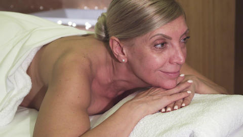 Beautiful woman relaxes lying on massage table Live Action