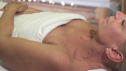 A relaxed woman is on the treatment in the spa salon Live Action