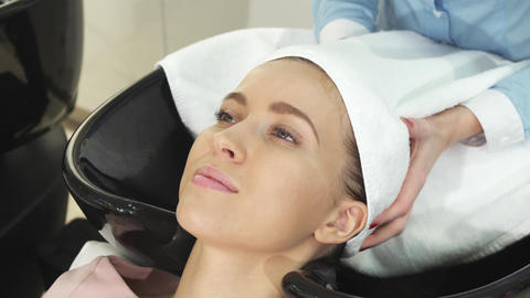 Beautiful young woman getting her wet hair wrapped in a towel by a professional hairdresser Live Action
