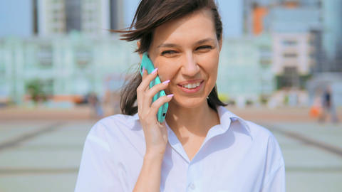 close up portrait happy cheerful woman laughing using cellphone urban city background Live Action