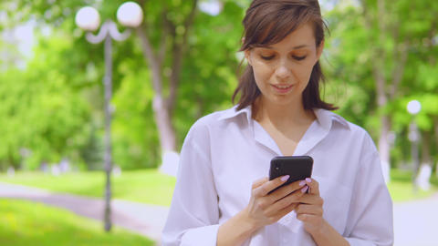 portrait millennials girl chatting online use cellphone in park Live Action
