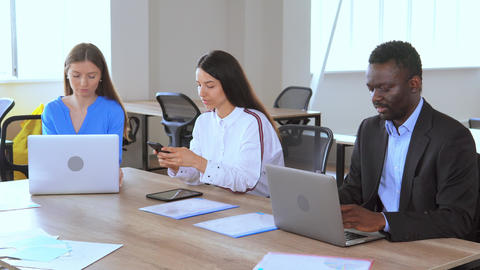 diverse employees sitting at the workplace staff using devices Live Action